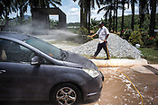 A guard sprays disinfectant while a car waits on a pool of bleached water to avoid any infections coming in or out of the pig farm at a highly protected pig farm in Ipoh, Perak, Malaysia on October 15th, 2016. <br /> In September 1998, a virus among pig farmers (associated with a high mortality rate) was first reported in the state of Perak in Malaysia. Dr. Chua investigated and discovered the virus and it was later named, Nipah Virus. The outbreak in Malaysia was controlled through the culling of &gt;1 million pigs.
