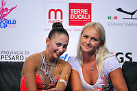 "(L-R) Daria Kondakova of Russia with coach smiles at ""kiss & cry"" at 2010 Pesaro World Cup on August 27, 2010 at Pesaro, Italy.  Photo by Tom Theobald."