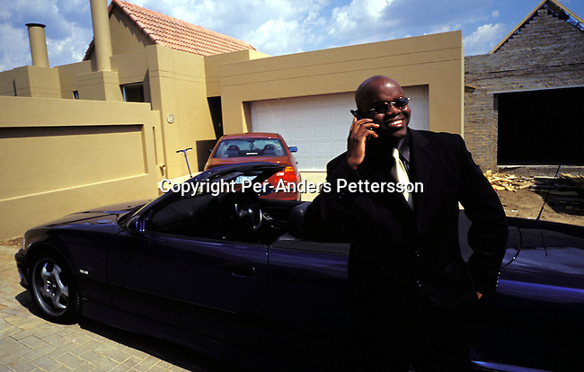 dilsbup00026 People. Buppy Oscar Dube a young successful black guy talking with a friend on his mobile phone outside his house before going to work on March 22, 2002 in Johannesburg, South Africa. He is working for Ericsson, the Swedish mobile phone equipment and phone maker in South Africa. He has reached the life that many blacks want. A nice house in a mainly white gated northern suburb, a beautiful wife, and daughter and a BMW 328I Convertible. Although, he likes his success, he often goes back to Soweto on weekends to wash his car and have a few beers with his friends and relatives. Many blacks that move to the northern suburbs quickly miss the notice and lively life in the township..Photo: Per-Anders Pettersson/iAfrika Photos