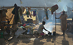 Anuak Ota cooks over a fire in a camp for over 5,000 internally displaced persons in an Episcopal Church compound in Wau, South Sudan. Most of the families here were displaced by violence early in 2017, after a larger number took refuge in other church sites when widespread armed conflict engulfed Wau in June 2016.<br /> <br /> Norwegian Church Aid, a member of the ACT Alliance, has provided relief supplies to the displaced in Wau, and has supported the South Sudan Council of Churches as it has struggled to mediate the conflict in Wau.