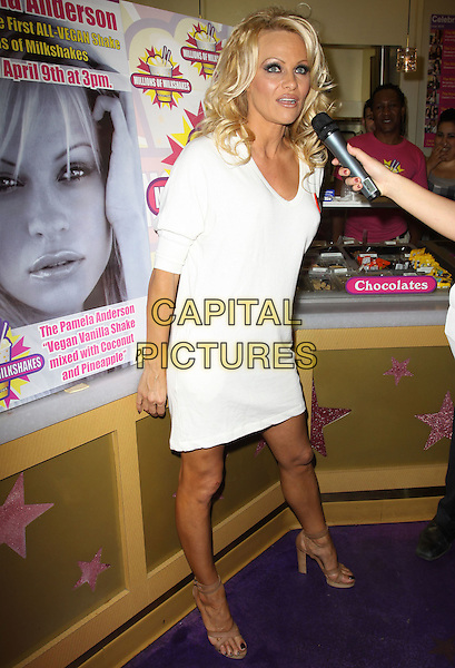PAMELA ANDERSON .Pamela Anderson Celebrates Her All-Vegan Shake At Millions Of Milkshakes held At Millions Of Milkshakes, West Hollywood, California, USA, .9th April 2010. .full length white  v-neck dress tanned brown ankle strap open toe sandals poster inside microphone interview beige .CAP/ADM/KB.©Kevan Brooks/AdMedia/Capital Pictures.