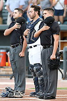 Catcher Scott Manea (25) of the Columbia Fireflies stands for the national anthem between umpire Tom Fornarola, left, and umpire Josh Gilreath before a game against the Charleston RiverDogs on Tuesday, August 28, 2018, at Spirit Communications Park in Columbia, South Carolina. Columbia won, 11-2. (Tom Priddy/Four Seam Images)