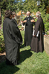 Fr. Dane Popovich shows his bee apiaries in his back yard to guests.