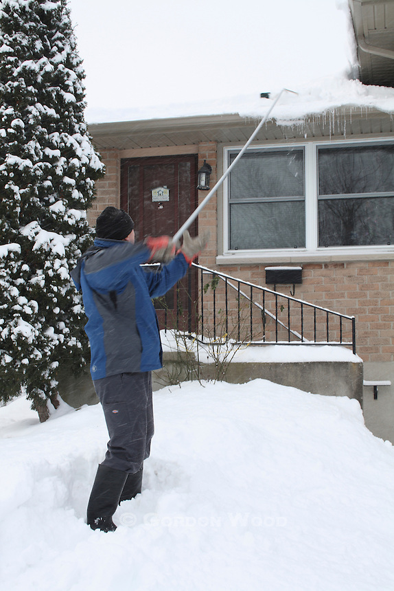 Raking Snow Off Residential Roof After Snowstorm
