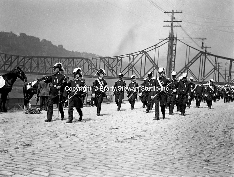 Pittsburgh PA:  Pittsburgh-area Manson marching in the annual St Patrick's Day Parade - 1903.  View of Homer Stewart and fellow Masons marching down Water Street with the Wabash Bridge in the background
