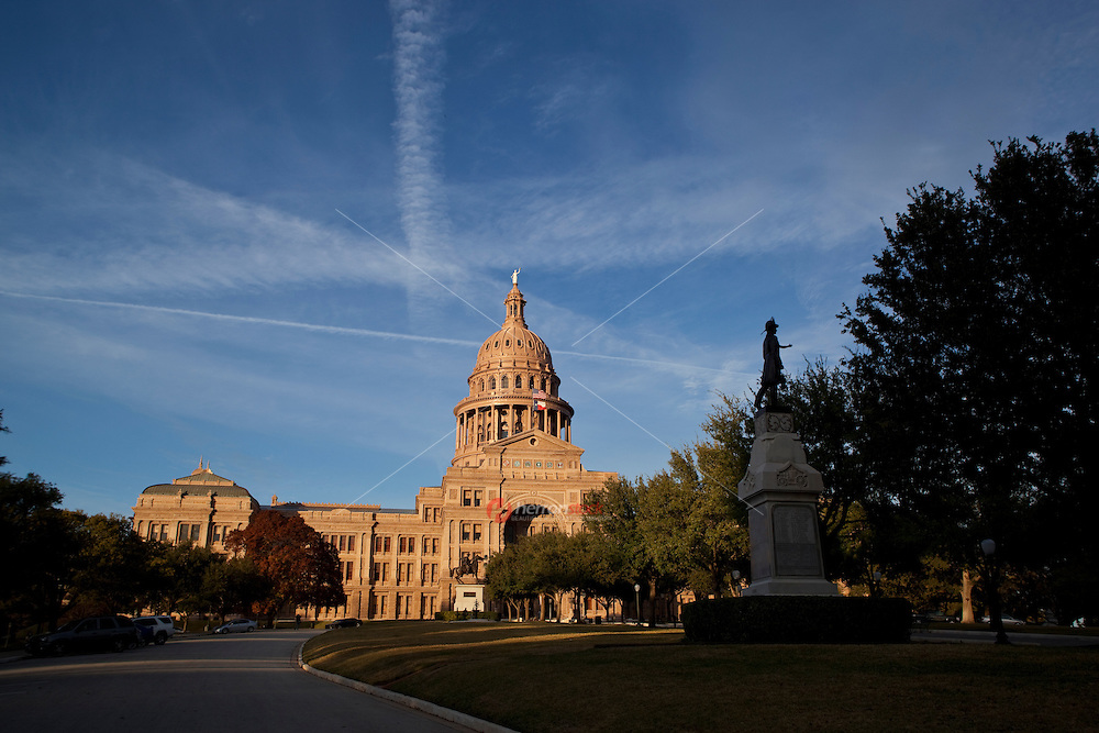 Wide angle view of the Texas State Texas Capitol outlined with national registered monuments, USA and Texas flags and the Goddess of Liberty statue atop the capitol dome, Austin, Texas, USA