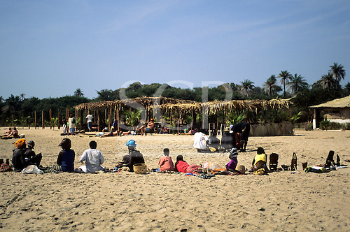 Banjul, The Gambia. Line of Gambians on the beach selling souvenirs and snacks to the tourists who have come to enjoy the sun.
