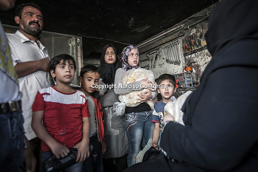 Syrian children and civilians await scared as they take refugee inside a mechanic workshop during an aircraft shelling in Qadi-Askar neighborhood at the northeast of Aleppo City.