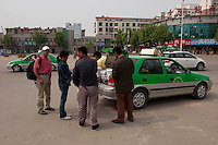 Daytime landscape view of people overloading the trunk of a taxi cab on Wei Wu Da Dao in front of the Bozhou Train Station in Bozhou in Qiáochéng Qū in Anhui Province.  © LAN