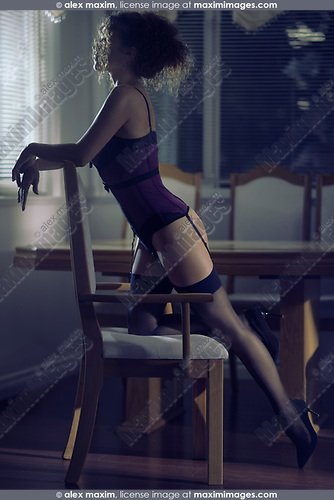 Sensual boudoir portrait of a sexy young woman in a corset and stockings leaning against a chair in a dimly lit living room at night
