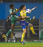 Nigeria defender (13) Christie George tries to clear the ball away from  Sweden midfielder (8) Charlotta Schelin. Sweden (SWE) tied Nigeria (NGA) 1-1 during a FIFA Women's World Cup China 2007 opening round Group B match at Chengdu Sports Center Stadium, Chengdu, China, on September 11, 2007.