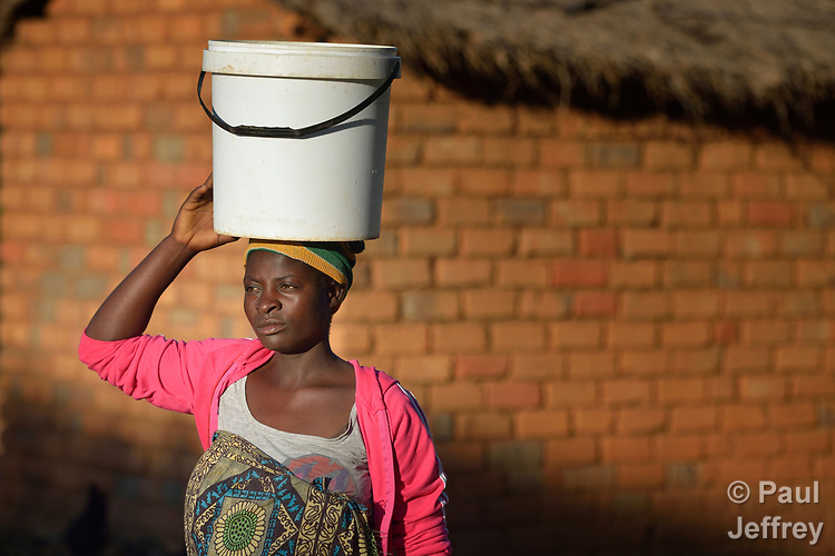 Misuzi Tembo carries water to her home in Kayeleka Banda, Malawi. Pregnant with her first child, she receives support from the Maternal, Newborn and Child Health program of the Livingstonia Synod of the Church of Central Africa Presbyterian. Tembo's husband has a job in South Africa and sends home money to support her.