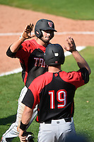 Tampa Spartans second baseman Ty Cooler (5) high fives Stephen Dezzi (19) after scoring the game typing run during an exhibition game against the Philadelphia Phillies on March 1, 2015 at Bright House Field in Clearwater, Florida.  Tampa defeated Philadelphia 6-2.  (Mike Janes/Four Seam Images)