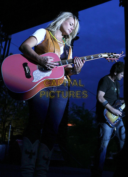 MIRANDA LAMBERT .Performs Poolside at the Silverton  Hotel and Casino, Las Vegas, Nevada, USA, .24th July 2009..country music live on stage gig concert half 3/4 length jeans waistcoat cowboy boots jeans pink tan leather white t-shirt top  playing guitar neon necklace .CAP/ADM/MJT.©MJT/Admedia/Capital Pictures