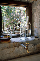 Glass bottles and a decanter line the ledge of a kitchen window which overlooks a garden filled with olive trees