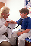 Young boy listens to pediatricians heart in examination room