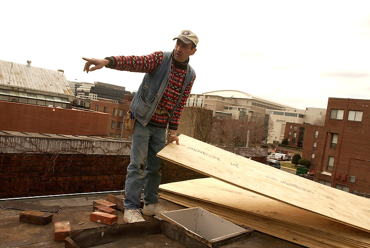 Irakli Chachanicze prepares to move plywood the roof of a townhouse on 6th Street, NW.  The house will be featured on This Old House.  The DC Convention Center appears in the background.
