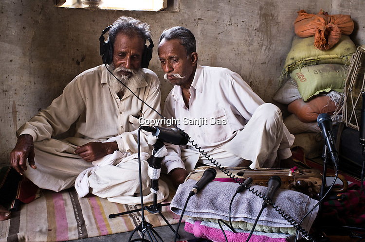 Atam Khan (71) and his younger brother, 66-year-old Manganiyar artist, Lakha Khan (right) listen to the field recordings of their performance in their house in Raneri village of Jodhpur district in Rajasthan, India. Photo: Sanjit Das/Panos