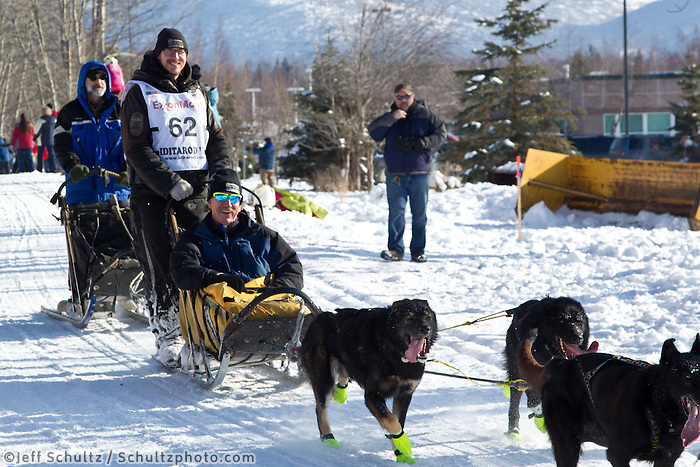 Brent Sass and team run past spectators on the bike/ski trail during the Anchorage ceremonial start during the 2013 Iditarod race.    Photo by Britt Coon/IditarodPhotos.com