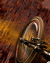 A close up of a bicycle front tire seen from above, riding across a circuit board textured landscape.