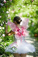 A girl dressed as a fairy smelling roses in the garden