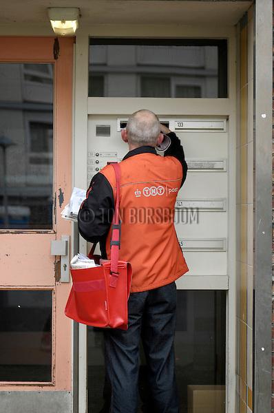 UTRECHT - Een senior postbode van TNP Post, het voormalige TPG, bestelt gestoken in oranje TNT-kleding met ouderwetse rode TPG tas, brieven bij mensen thuis. COPYRIGHT TON BORSBOOM