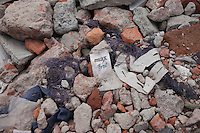 "A clothes tag named ""Max Boy"" lies in the rubble of a garments factory that collapsed in Savar, near Dhaka, Bangladesh"