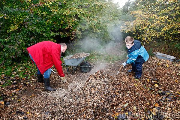 Landelijke natuurwerkdag. Vrijwilligers helpen met werkzaamheden in de natuur. Houtsnippers scheppen