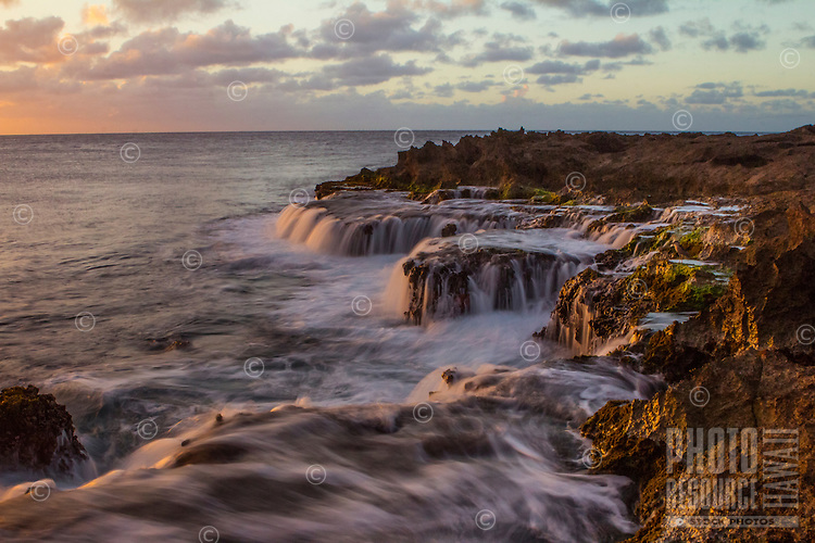 A long exposure at sunset captures the soft look of water receding from the rough shore at Pupukea Beach Park on the North Shore of O'ahu.