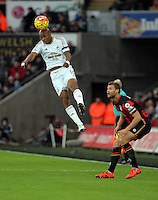 Andre Ayew of Swansea heads the ball (L) during the Barclays Premier League match between Swansea City and Bournemouth at the Liberty Stadium, Swansea on November 21 2015