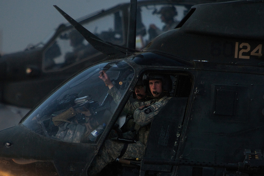 "CW3 Chuck Macglothlin and his co-pilot sitting at a refueling point waiting to take on gas after a mission. In the background an AH-64 Apache attack helicopter flying as Macglothin's wingman also refuels..The pilots of Charlie and Bravo Troops 2nd Squadron 17th Cavalry Regiment - part of the 101sst Airborne Division - fly missions over the critically contested landscape of Kandahar in their OH-58 Kiowa Warrior scout-attack helicopters. Thinking of themselves as the ""infantry of the sky,"" 2/17 CAV's mission is to fly low and fast over the battlefield relaying reconnaissance information to ground-bound troops - scanning for the enemy, looking for signs of IED placement, reporting on the movements and activities of civilians - and bringing their ship's rockets and machine-guns to bear on enemy fighters when they can be found.."