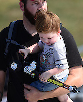Sept. 23, 2012; Ennis, TX, USA: NHRA fan holds toy dragster with father during the Fall Nationals at the Texas Motorplex. Mandatory Credit: Mark J. Rebilas-