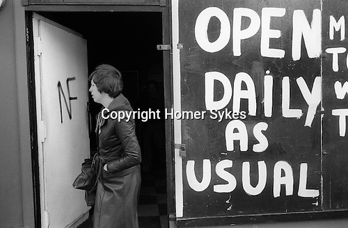 Hoxton east London. Boarded up shop, Open Daily as Usual. Boarded up because of violence anticipated in the area. NF National Front graffiti onto the shops front door.<br />