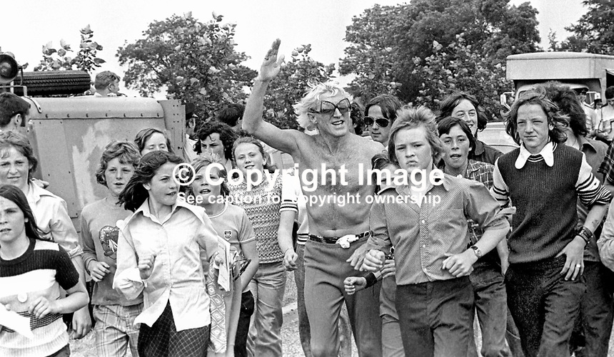 Pop idol &amp; disc jockey Jimmy Savile heads a Safari Walk from Mallusk, Glengormley, Newtownabbey, N Ireland, to Nutt's Corner for a pop concert on 30th June 1974. 1974063000366b<br />