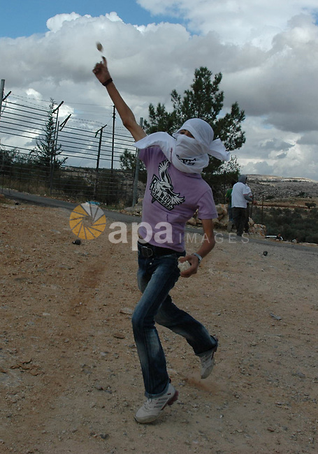 A Palestinian protestor throws stones towards Israeli soldiers  during a demonstration against Israel's separation barrier in the West Bank village Billin near Ramallah on Nov 13, 2009. Photo by Nedal Shtieh