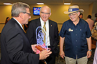 12 August 2011:  FIU Biscayne Bay Campus Vice Provost Steve Moll (left) shows an illuminated etching of an FIU football helmet to FIU Alumni Association Director Bill Draughon (center) and FIU President Mark Rosenberg (right) during the FIU 2011 Panther Preview at University Park Stadium in Miami, Florida.