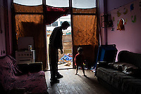 Man looks after his nephew in the house of his brother in Osterode IDP camp in northern Mitrovica. Before they were converted to houses, these rooms were used as garages or warehouses by the French army.