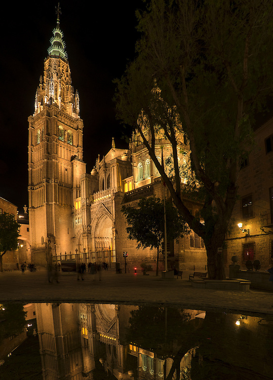 Reflected in a small pool, the beautifully illuminated ornate cathedral in Toledo is dramatically displayed.