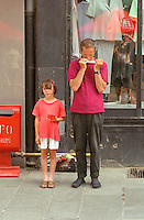 Father and daughter street musicians ages 40 and  7 playing harmonica.  Torun Poland