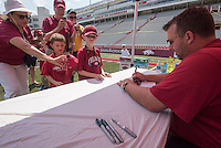 NWA Democrat-Gazette/J.T. WAMPLER University of Arkansas head football coach Bret Bielema signs autographs Sunday Aug. 16, 2015 for Riley Vick(left), 6, and his brother Eli Vick, 9 of Conway while their grandparents Bruce and Brenda Vick of Fort Smith take photographs during 2015 UA Fan Day. Hundreds of people descended on Donald W. Reynolds Razorback Stadium to get autographs and talk to Razorback football players and coaches.