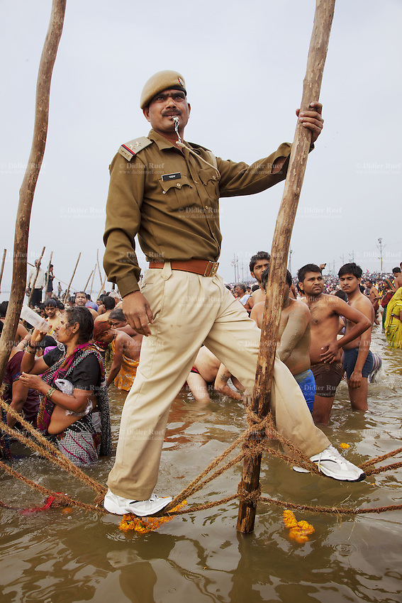 "India. Uttar Pradesh state. Allahabad. Maha Kumbh Mela. Royal bath on Basant Panchami Snan (fifth day of the new moon) under a policeman's supervision. The ritual ""Royal Bath"" is timed to match an auspicious planetary alignment, when believers say spiritual energy flows to earth. Pilgrims and devotees celebrate their faith by taking a dip at Sangam and worshiping the river Ganges. A woman wearing a saree drinks the water from the river in a plastic bottle. The Kumbh Mela, believed to be the largest religious gathering is held every 12 years on the banks of the 'Sangam'- the confluence of the holy rivers Ganga, Yamuna and the mythical Saraswati. In 2013, it is estimated that nearly 80 million devotees took a bath in the water of the holy river Ganges. The belief is that bathing and taking a holy dip will wash and free one from all the past sins, get salvation and paves the way for Moksha (meaning liberation from the cycle of Life, Death and Rebirth). Bathing in the holy waters of Ganga is believed to be most auspicious at the time of Kumbh Mela, because the water is charged with positive healing effects and enhanced with electromagnetic radiations of the Sun, Moon and Jupiter. The Maha (great) Kumbh Mela, which comes after 12 Purna Kumbh Mela, or 144 years, is always held at Allahabad. Uttar Pradesh (abbreviated U.P.) is a state located in northern India. 15.02.13 © 2013 Didier Ruef"