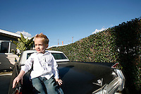 Young Boy Sitting On A Black Classic Cadillac