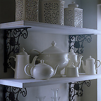 Open shelves on ornate metal brackets display a collection of white teapots and jars in the kitchen