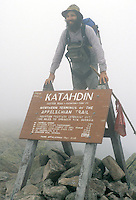 AJ2232, hiker, summit, Appalachian trail, Maine, A thru hiker (man) standing at the terminus (end or start) after finishing the Appalachian Trail. Sign on the summit of Mt. Katahdin in Baxter State Park.