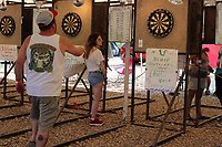 """MEGAN DAVIS/MCDONALD COUNTY PRESS Darters of all ages gathered under the white-top tent on Saturday to hone their skills and share their passion, many of them sporting shirts from past Chicken Coop Open events. Local businesses are integral to the event as many of them sponsor dart boards. """"Because of these sponsors we're able to keep the Chicken Coop in Noel,"""" said organizer Mike Edwards."""