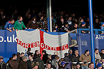 "Portsmouth 1 Southampton 1, 18/12/2012. Fratton Park, Championship. Portsmouth fans in the North Stand unfurling a club flag at Fratton Park stadium before their club take on local rivals Southampton in a Championship fixture. Around 3000 away fans were taken directly to the game in a fleet of buses in a police operation known as the ""coach bubble"" to avoid the possibility of disorder between rival fans. The match ended in a one-all draw watched by a near capacity crowd of 19,879. Photo by Colin McPherson."