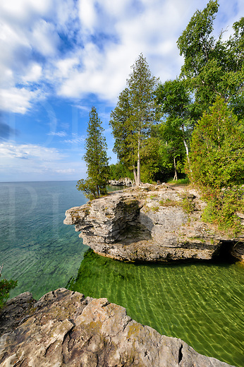 This was a very beautiful calm day along the western shore of Lake Michigan and I was quite glad to be there at this small park in Door County, Wisconsin. The layers of dolomite lie flat horizontally and the water has worn shallow caves and eroded cliffs into it, hence the name, Cave Point Park. In places, the rock strata lying even with the waterline serves as a &ldquo;beach&rdquo; that you can walk out to the lake lapping even at the very edge, like a nearly overflowing bathtub.<br /> <br /> The water in this image is green from the many tall cedars growing close to the cliff edges reflected into it. It is very clear and deep, and you can see the large rocks twenty feet down to the bottom. This little park attracts hikers and kayakers to enjoy nature in an idyllic place, but when the weather turns and the wind and rain comes, it's an entirely different story! The lake can be furious and smashing hard against these rocks trying to reduce them to sand as it has always done, and in winter everything is coated in white ice from the spray. <br /> <br /> Monthly Newsletter sign up at Dierks Photo on Facebook...