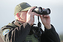 Dec 1, 2015:  Fish and Wild Life officer Bryan Davidson uses binoculars to look at fisherman on the waters in front of Fort Flagler State Park in Port Townsend, WA.