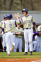 Austin Neary (33) of the Western Carolina Catamounts high fives teammate Aaron Attaway (2) after he scored a run in the first inning against the Davidson Wildcats at Wilson Field on March 10, 2013 in Davidson, North Carolina.  The Catamounts defeated the Wildcats 5-2.  (Brian Westerholt/Four Seam Images)