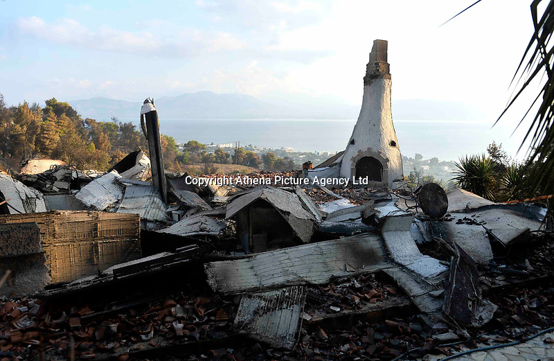 Pictured: A damaged house in the area.<br /> Re: A forest fire has been raging in the area of Kalamos, 20 miles north-east of Athens in Greece. There have been power cuts, country houses burned and children camps evacuated from the area.